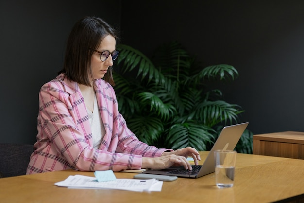 European confident business woman in a pink jacket and with a laptop in her office working