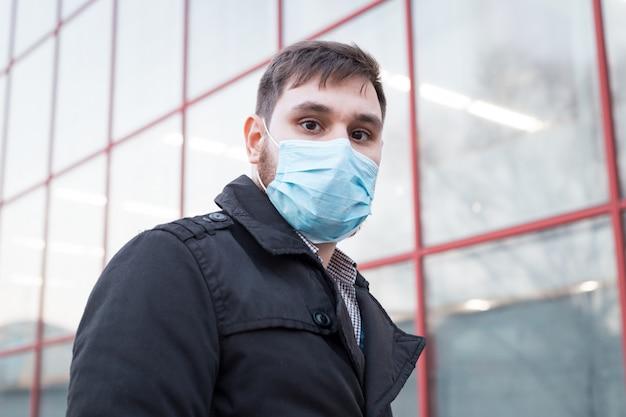 Европейский коронавирус. портрет кавказского человека нося лицевую гигиеническую маску, маску респираторной защиты outdoors. вирус, защита от коронавирусов, загрязнение воздуха, экология, экологическая осведомленность.