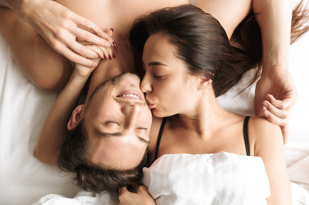 European couple 30s hugging together, while lying in bed at home or hotel apartment