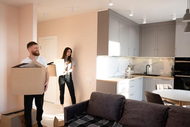 Европейская пара, несущая картонные коробки с вещами дома. концепция переезда в новую квартиру. идея молодой семьи. красивая девушка и бородатый мужчина. интерьер однокомнатной квартиры. солнечный день