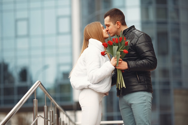 ヨーロッパのカップルは花と一緒に立っています。