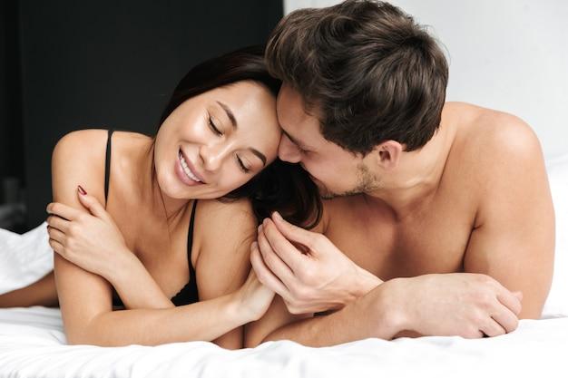 집이나 호텔 아파트에서 침대에 누워있는 동안 유럽 부부 남자와 여자가 함께 포옹