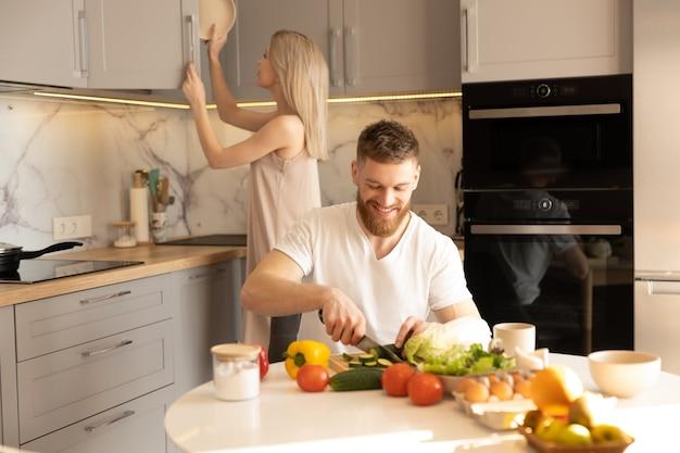 台所のヨーロッパのカップル。材料でテーブルでキュウリを切る男。木製の食器棚にプレートを置く女性。若い家族のアイデア。健康的な栄養の概念。モダンなアパートのインテリア