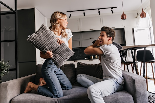 Европейская пара позирует во время боя подушками. крытый портрет смеющихся молодых людей, отдыхающих в гостиной.