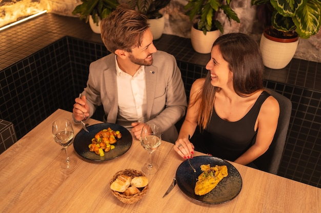 European couple in a restaurant, having fun having dinner together with food, celebrating valentine, overhead shot from above