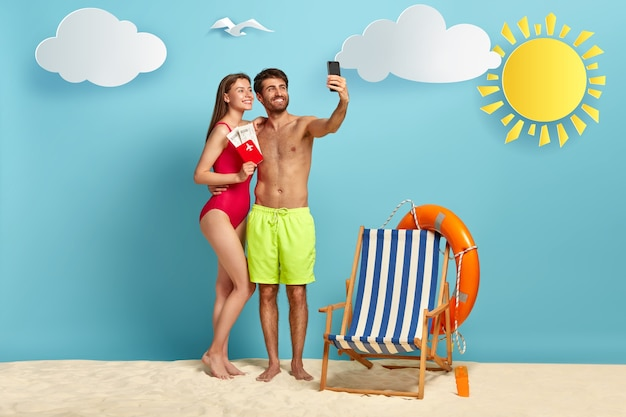 European couple takes selfie on cell phone, pose on beach with passport and flying tickets