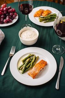 ヨーロッパ料理。サーモンステーキとアスパラガス、野菜サラダ、ソース、ブドウ、パンと赤ワインのグラス。キッチンでの2人での夕食