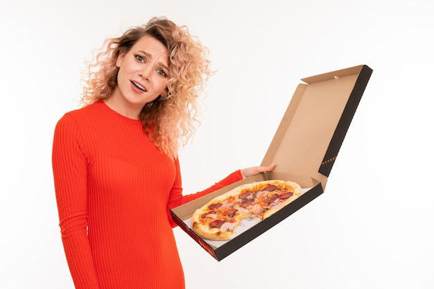 European curly blonde girl in a red dress holds a box of pizza