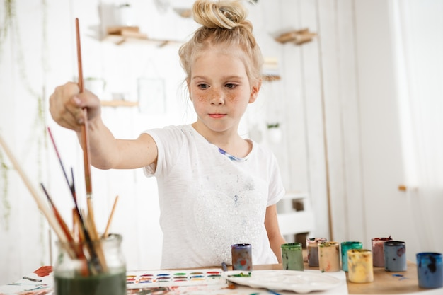 European cute creative child with hair bun snd blue eyes occupied with drawing.