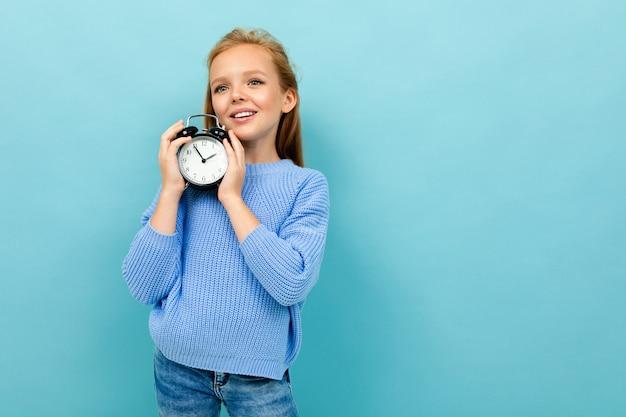 European cute girl holding an alarm clock in her hands on light blue