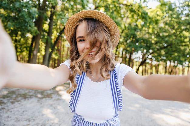 Ragazza carina europea con capelli ondulati in posa giocosamente nel parco. incantevole signora con cappello che fa selfie con alberi
