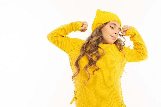 European cute girl in yellow clothes wakes up and stretches on white with copyspace