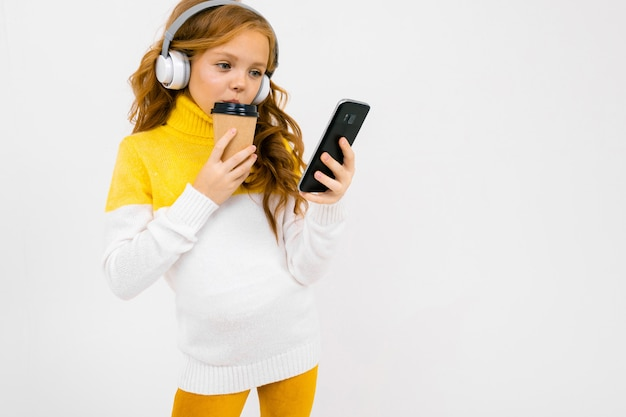 European cute young girl in white headphones looks at the phone and holds a glass