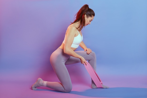 European dark haired wearing sporty white short top and gym leggings makes exercises for triceps with sport fitness rubber bands isolated over color background, looking down, stands on one knee.