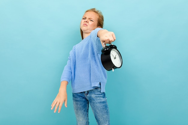 European disgruntled girl holding an alarm clock on light blue