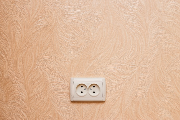 European electric outlet on wall covered with wallpaper