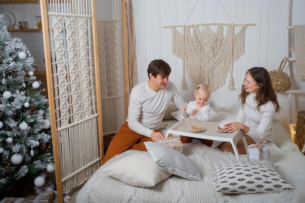 Европейская семья завтракает в постели с подарками