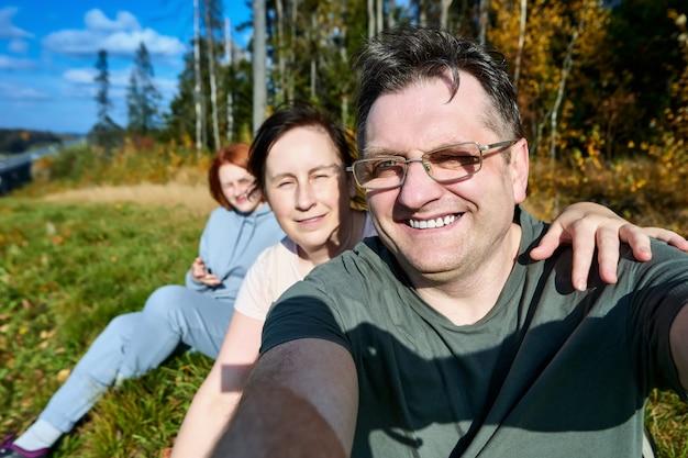 ヨーロッパの家族が森に座って自分撮りをしている