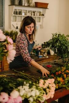 花柄のデザインスタジオで生け花を作る緑のエプロンを持つヨーロッパの女性花屋
