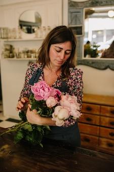 꽃 디자인 스튜디오에서 꽃꽂이를 하는 녹색 앞치마를 입은 유럽 여성 꽃집