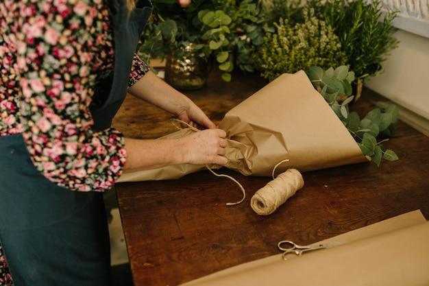 꽃 스튜디오에서 꽃꽂이를 만드는 녹색 앞치마와 유럽 여성 플로리스트