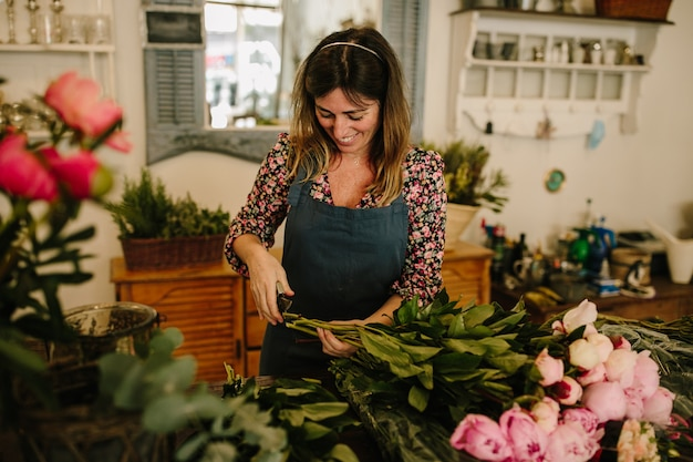 フラワーアレンジメントを作る緑のエプロンを持つヨーロッパの女性の花屋