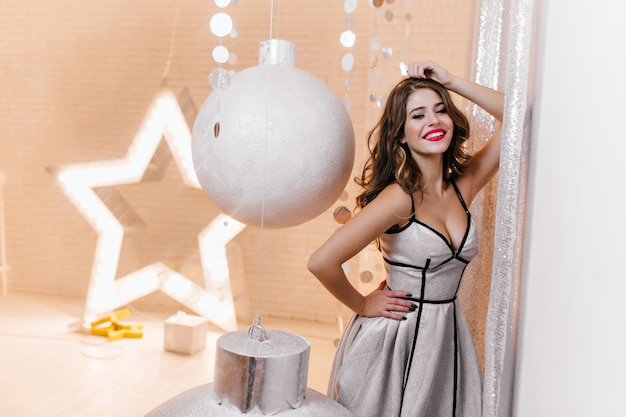 European female model with beautiful curls in festive outfit coquettishly posing surrounded by large silver christmas toys