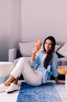 La donna blogger di moda bruna europea in forma si siede sul pavimento nel soggiorno vicino al divano con il telefono