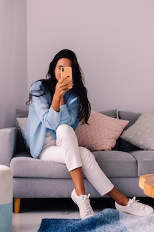 Donna europea blogger moda bruna in forma si siede sul pavimento nel soggiorno vicino al divano