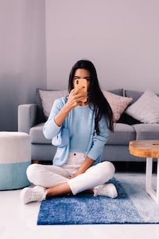 ヨーロッパのフィットブルネットファッションブロガーの女性は、電話でソファの近くのリビングルームの床に座っています