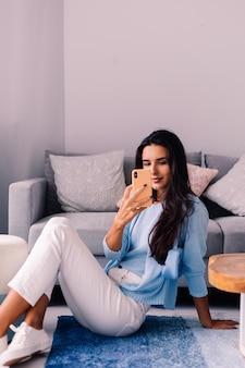Европейская подтянутая брюнетка модный блоггер сидит на полу в гостиной возле дивана с телефоном