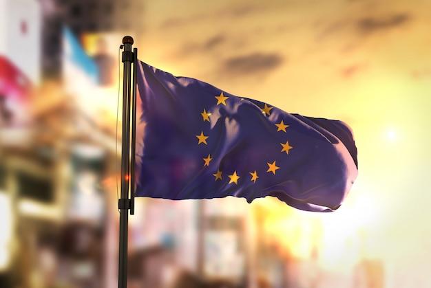 Европейский флаг против городского размытого фона при восходе солнца