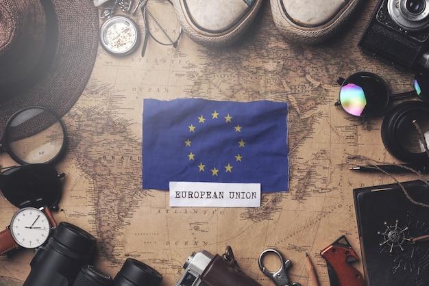 European flag between traveler's accessories on old vintage map. overhead shot