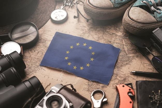 European flag between traveler's accessories on old vintage map. tourist destination concept.