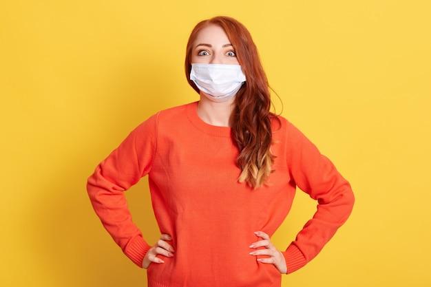 医療用マスクとオレンジ色のセーターを着て、黄色い壁に立ち、腰に手を当て、大きな目で見ているヨーロッパの生姜の若い美しい女性は、何か衝撃的なものを見ています。