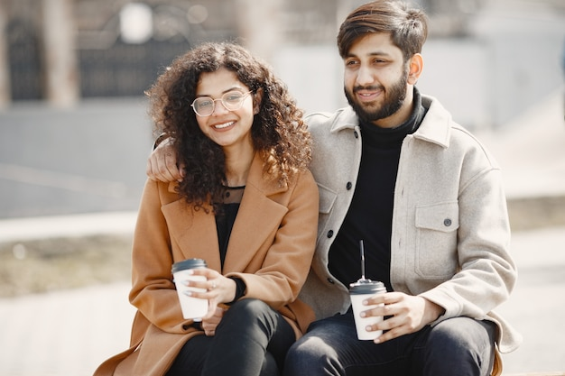 유럽 소녀 anindian 남자 타고 스쿠터와 미소. 커피를 마시는 사람.