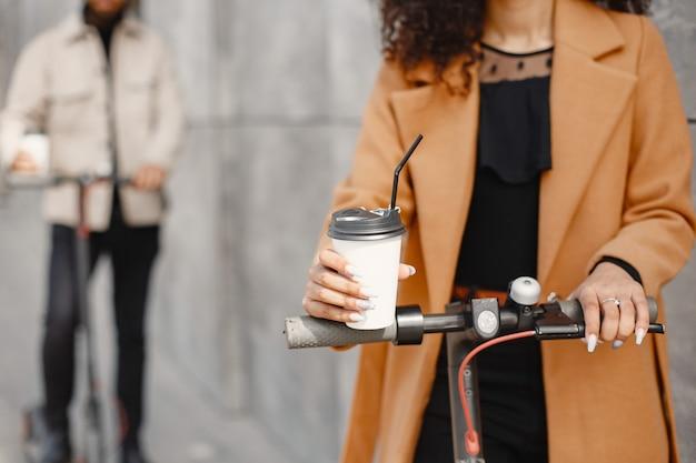 ヨーロッパの女の子anindian男はスクーターに乗って笑顔。コーヒーを飲んでいる人。