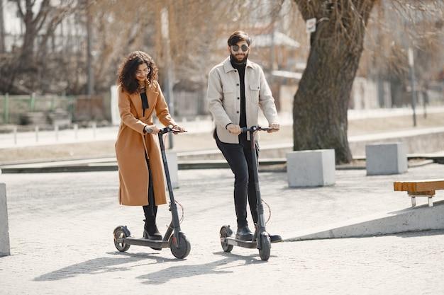 Европейская девушка и индийский парень катаются на скутерах и улыбаются.