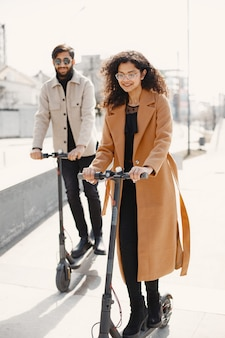 European girl anindian guy ride scooters and smile.