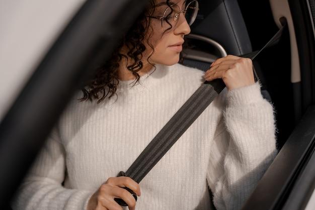ヨーロッパの女の子が車のシートベルトを締めます。眼鏡をかけている集中した若い巻き毛の女性。車の運転の概念