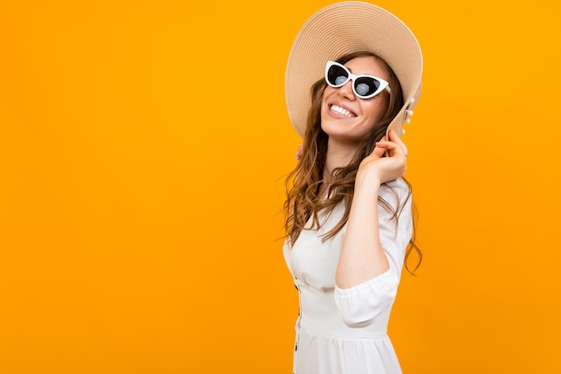 European girl in hat and glasses you a white dress