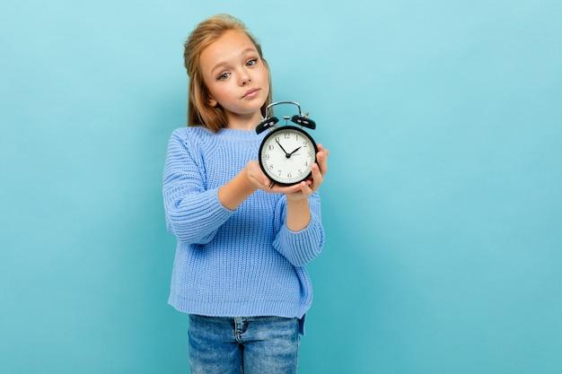 European girl holding an alarm clock on light blue