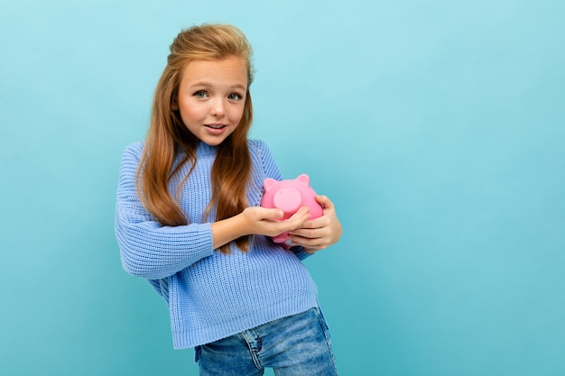 European girl holding a piggy bank in her hands on light blue wall with copyspace