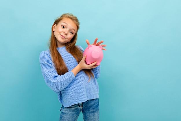 European girl holding a piggy bank in her hands on light blue wall.