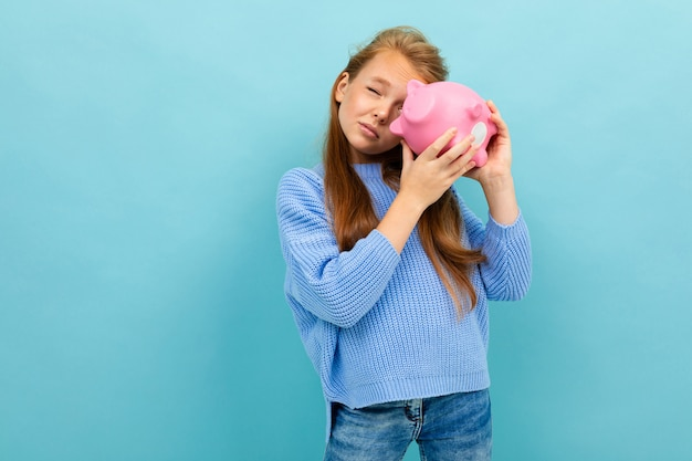 European girl holding a piggy bank in her hands on light blue
