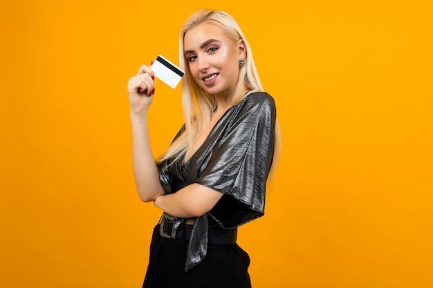 Европейская девушка держит кредитную карту с макетом на желтой поверхности студии