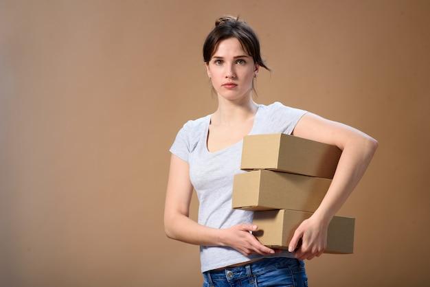 ヨーロッパの女の子は彼女の側で彼女の手でいくつかのボックスを保持し、ベージュの壁に直接カメラを見て