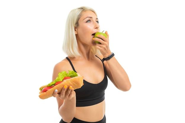 Европейская девушка в спортивной форме показывает яблоко и фаст-фуд