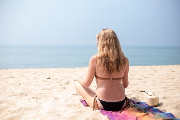 Европейская девушка в купальнике, с длинными светлыми волосами, сидит в позе лотоса на песке