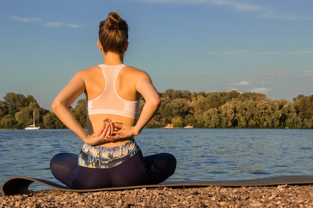 A european girl in a light tracksuit practices yoga on the river bank on a rubber yoga mat